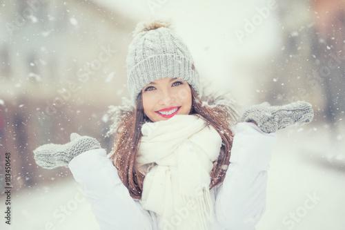 Piękna uśmiechnięta młoda kobieta w ciepłej odzieży. Pojęcie portret w zimy śnieżnej pogodzie