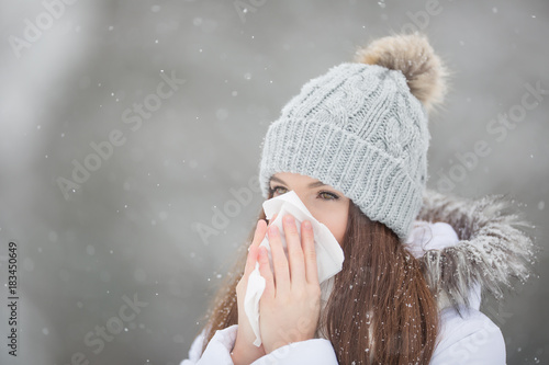 Foto Murales Girl with allergy symptom blowing nose. Teen girl using a tissue in a winter park