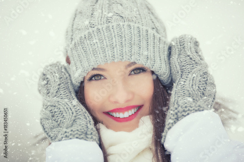 Foto Murales Beautiful smiling young woman in warm clothing. The concept of portrait in winter snowy weather