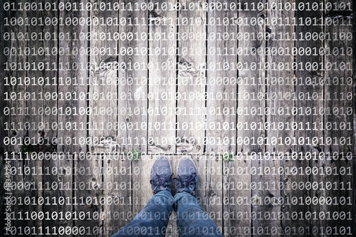 Man standing on aged wooden planks floor with binary numbers. Point of view perspective used. Conceptual personal security data background.