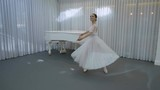 The young ballerina trains to do fouette on her left leg in the bright class. The dancer wears long white tutu and pointe and does several right turns during the repetition. The grand piano, the big - 183453858
