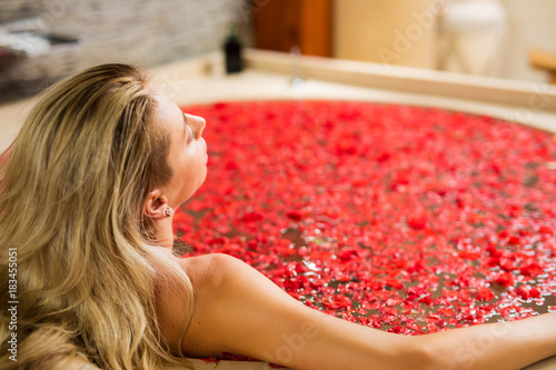 Woman enjoying red flower bath