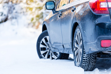 Winter tires. Black Subaru Outback rear view on snowy forest road. Winter conditions.