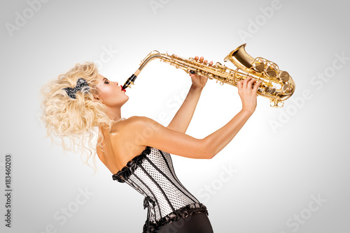 Playing jazz / Beautiful pinup model playing saxophone on grey background Poster