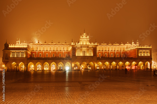 Market hall at main Cracow square at misty night with golden sky