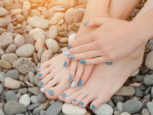 Plexiglas Manicure Female feet and hands with a blue manicure on pebbles