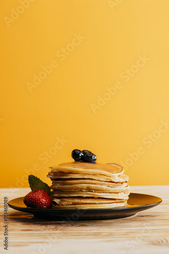 Sticker stack of delicious pancakes with berries on yellow
