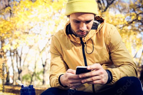 Sports man typing messages. Autumn season.