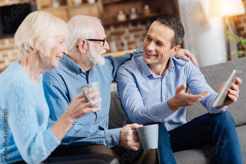 Pleasant discussion. Handsome young man sitting on the sofa next to his senior parents, holding a tablet in his hand and having a discussion with them while they drinking coffee