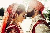 Indian groom dressed in white Sherwani and red hat with stunning bride in red lehenga stand outside and kiss each other tender in the rays of light