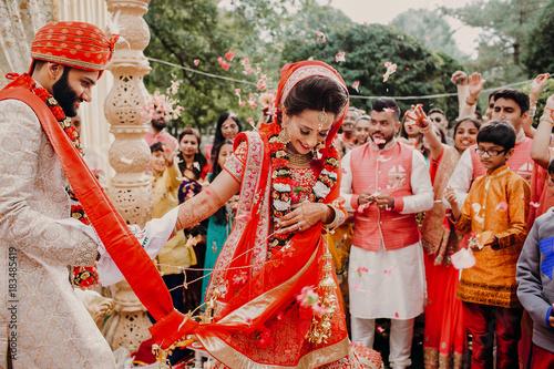 Foto Murales Indian groom dressed in white Sherwani and red hat with stunning bride in red lehenga during the Saptapadi ceremony on Hindu wedding