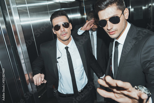 Foto Murales bodyguards stopping paparazzi and celebrity covering face with hand in elevator