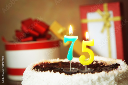 Seventy five years birthday. Cake with burning candles and gifts Poster