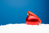 Christmas ball with red ribbon on artificial snow - 183488091