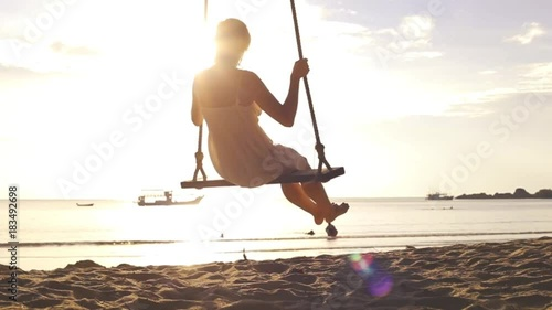 Slow motion footage of happy woman on rope swing at the beach during vacation holidays and crossing the sun, travel destination leisure concept