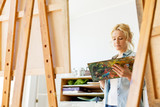 woman with easel painting at art school studio - 183493205