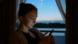Woman using smartphone in cabin of cruise ship. Evening time, lowlight. Technology and journey concept - 183508437