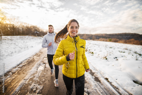 Beautiful happy active runner girl jogging with her personal handsome trainer on a snowy road in nature.