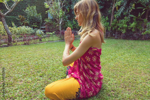 Sticker Young woman practicing yoga in tropical garden.