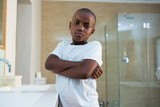 Portrait of boy standing by sink with arms crossed - 183513036