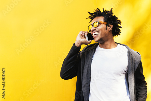 Portrait of handsome afro man using his mobile.