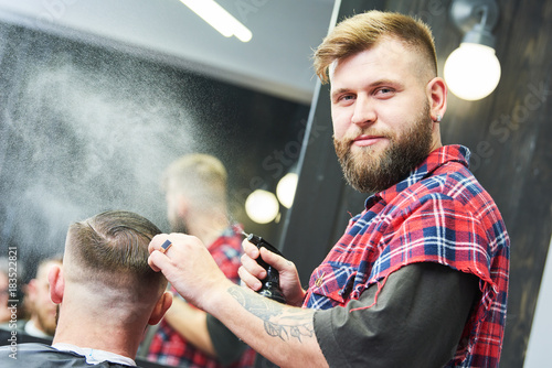 Barber at work. Hairdresser cutting hair of client