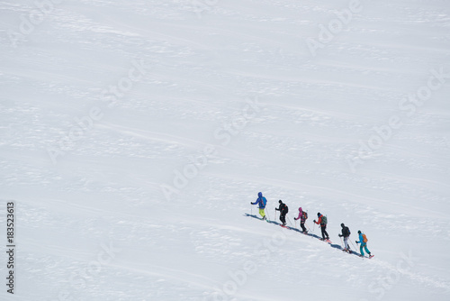 group of people exploring glacier or snowy land walking with snowshoes. Europe Alps Mont Blanc massif mount. Winter sunny day, snow, wide shot.Exploring and travelling