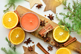 oranges with anisestars, cinnamon sticks, juniper branch and candle - 183525284