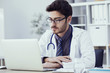 Portrait of doctor working on computer in medical office
