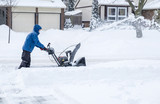 Man Removing Snow with a Snowblower in a Suburban Neighborhood - 183528858