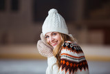 Autumn, Winter portrait: Young smiling woman dressed in a warm woolen cardigan, gloves and hat posing outside. - 183530637