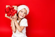 Happy smiling girl in Christmas cap holding Christmas gift in craft paper and with a red bow on a red background. Sale. Black friday. Shopping. Merry Christmas