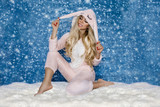 Beautiful sexy blonde woman wearing a pajama, a bunny costume, smiling happily. Fashion model on a winter background. - 183536282