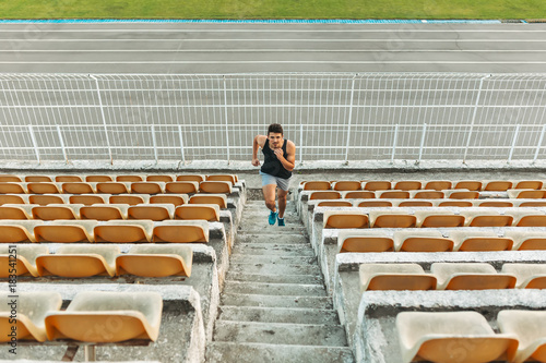 Plexiglas Fitness Image of young athletic man running by ladder at the stadium out
