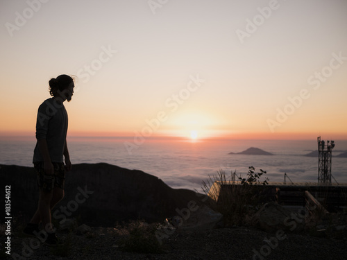 silhouette of man standing on the mountain above the clouds during sunset Poster