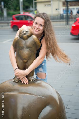 Sticker Woman smile at bronze male statue in wroclaw, poland