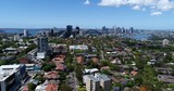 Lower North Shore residential suburbs with small houses and green streets towards Sydney Harbour and city CBD landmarks and high-rise towers.