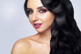 Beautiful woman portrait on gray background. Glamour make up and long curly hair. - 183556450