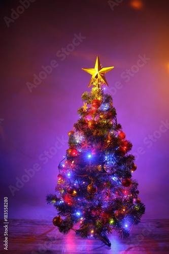Christmas tree with festive lights, purple background - 183558280