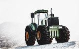 Large heavy duty green tractor on a mountain - 183559209
