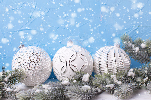 Three white balls and fur tree spruces against blue wall.