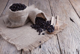 Coffee beans in bag with wooden spoon on old wood plank. - 183572674