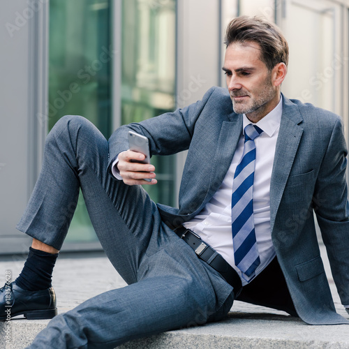 Fototapeta businessman sitting on stairs in an office park