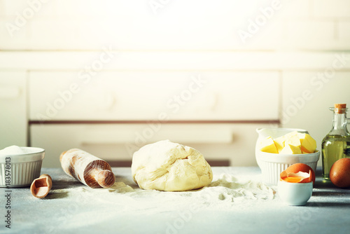 Baking background. Cooking ingredients for dough, eggs, flour, sugar, butter, rolling pin on white style kitchen. Copy space