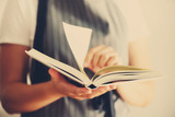 Girl wearing grey apron and reading book. Lifestyle concept - 183578459