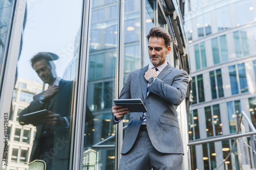 Fridge magnet businessman in an office park with a tablet in the hand