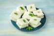Cucumber sandwiches with mint on teal blue background