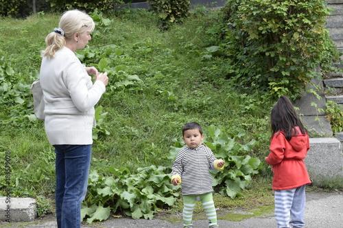 перуанская бабушка в городском парке с внуками