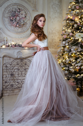 Beautiful young girl in a long dress on the background of a Christmas tree in a chic interior.