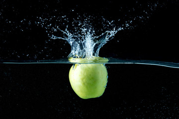 falling apple in water with spray on  black background